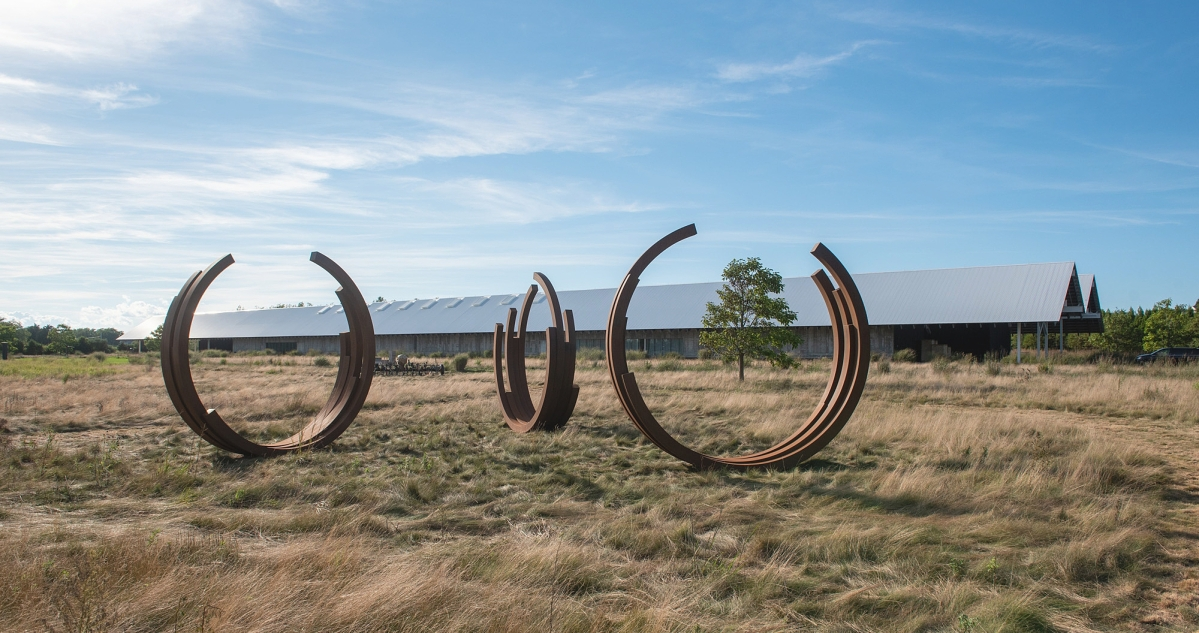 """Bernar Venet (French, b 1941), """"Arcs in Disorder: 220.5° Arc x 15,"""" 2006.   COR-TEN steel, 161-  by 163-  by 35-  inches each. Courtesy of the artist and Kasmin Gallery, New York. Installation view in the exhibition """"Field of Dreams,"""" Parrish Art Museum, Water Mill, N.Y.    —Timothy Schenck photo"""